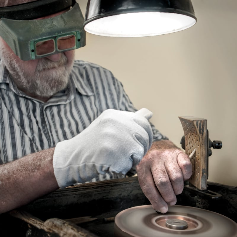 A gemstone cutter polishing a gemstone