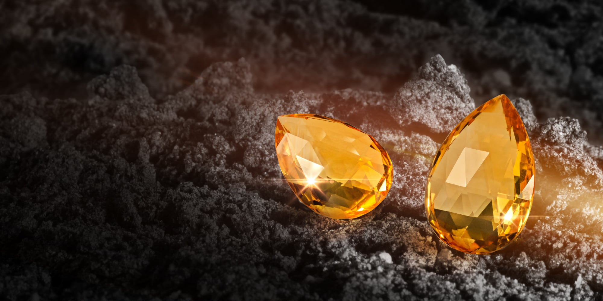 Citrine gemstones on dark sand